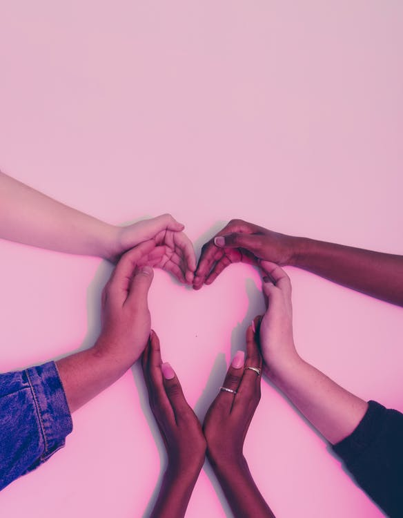 Five people joining hands to form a heart