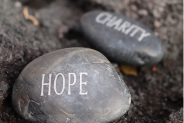 "A rock with ""Hope"" written on it next to a rock with ""Charity"" written on it"